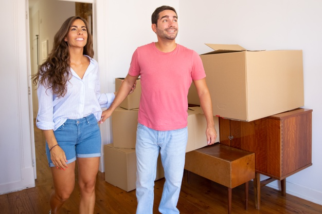 happy-excited-young-couple-looking-their-new-apartment-with-carton-boxes-furniture-smiling-talking_74855-9978