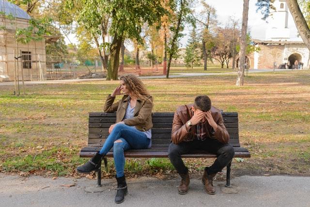 Nahnevaná žena a trpiaci sa muž, sediaci na lavičke
